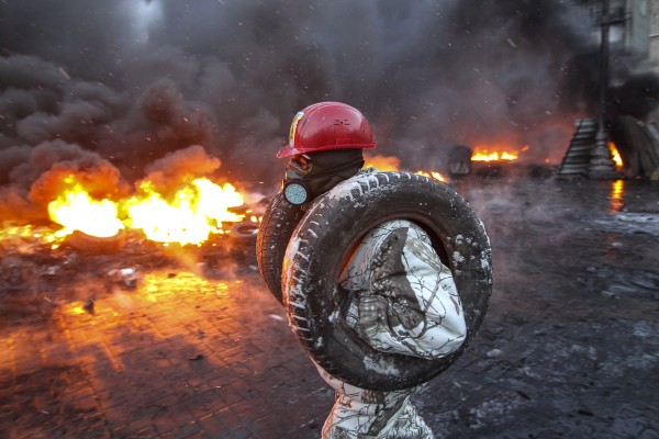 A pro-European integration protester carries tyres for burning at the site of clashes with riot police in Kiev January 23, 2014. Ukrainian opposition leaders emerged from crisis talks with President Viktor Yanukovich on Wednesday saying he had failed to give concrete answers to their demands, and told their supporters on the streets to prepare for a police offensive. REUTERS/Valentyn Ogirenko (UKRAINE - Tags: POLITICS CIVIL UNREST)